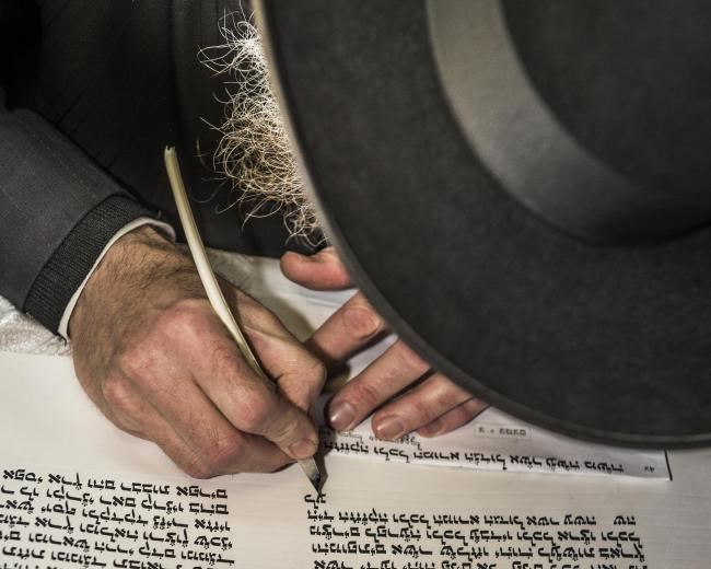 Photo of a Jewish man writing a Hebrew scripture