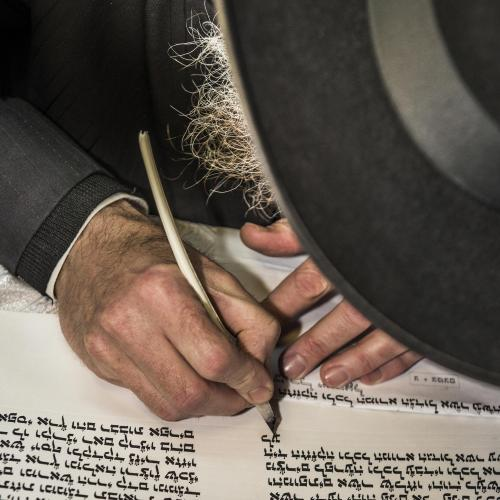 Photo of a Jewish man writing Hebrew scripture